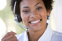 Young businesswoman wearing headset, smiling, portrait