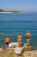 People in bathing suit standing in front of the transparent waters of Paxos Island, Greece