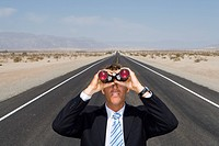 Businessman in middle of open road in desert, using binoculars, elevated view