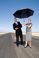 Businessman and woman on open road in desert with umbrella, man with laptop computer, low angle view