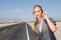 Businesswoman on side of road in desert, hand on earpiece, portrait, close-up