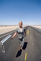 Businesswoman walking in middle of road in desert with briefcase, elevated view