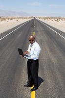 Businessman on line in middle of road in desert, using laptop computer, elevated view