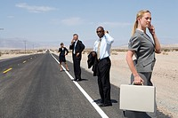 Small group of businessmen and women using mobile phones on side of road in desert, side view