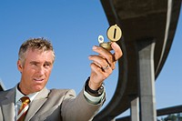 Businessman holding up compass beneath overpass, low angle view (thumbnail)