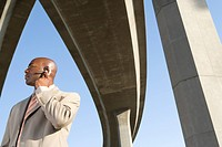 Businessman with hand on earpiece beneath overpasses, low angle view