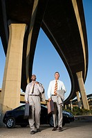 Two businessmen by car with briefcases beneath overpasses, low angle view