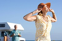 Mature woman with hands on hat by motor home on beach, husband in background, low angle view