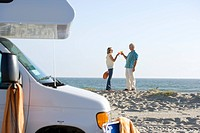 Mature couple toasting with cocktails by motor home on beach, side view