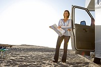 Mature woman with map by motor home on beach, smiling, low angle view lens flare