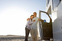 Mature couple arm in arm by motor home on beach, smiling, portrait, low angle view sun flare