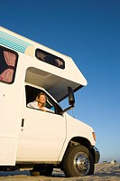Mature woman looking out window of motor home, low angle view