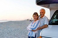 Mature man embracing woman by motor home on beach, smiling, portrait