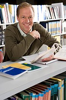 Man studying in library, smiling, portrait, close-up