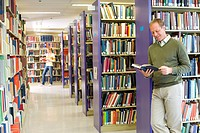 Man in library looking at book, smiling