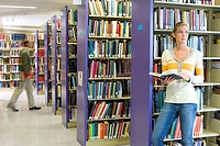 Woman with book in library (thumbnail)