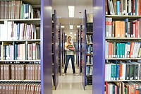 Young woman with armful of books in library, smiling, portrait (thumbnail)