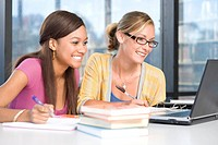 Female students studying with laptop computer, smiling