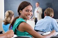 Students at desks in classroom, teacher by board, portrait of young woman smiling