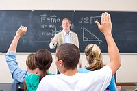 Students with arms raised in classroom, teacher by blackboard smiling, rear view