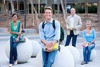 Teenage school students 16-18 sitting on concrete balls outdoors by male teacher, smiling, portrait