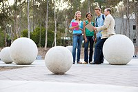 Teenage school students 16-18 in conversation with male teacher on concrete ball outdoors
