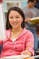Young woman with earphones at computer, smiling, portrait
