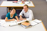 Male and female students studying at table, smiling, portrait, elevated view