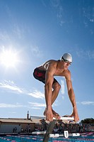 Male swimmer on starting block, low angle view sun flare