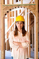 Woman in hardhat with arms crossed in partially built house, portrait