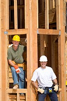 Builders on site, smiling, portrait