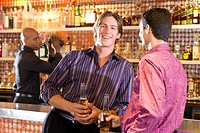 Young man and friend at bar with drinks, smiling, portrait