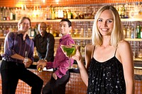 Young man and friend at bar looking at woman with cocktail, smiling, portrait (thumbnail)