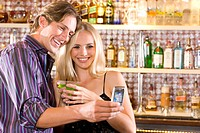 Young couple at bar with drinks, taking photograph of themselves, smiling
