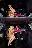 Young couple in limousine, smiling at each other