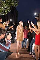 Young woman surrounded in people taking photographs, low angle view