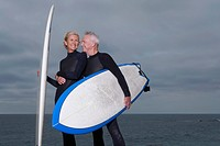 Male and female surfers with surfboards by beach, man´s arm around woman