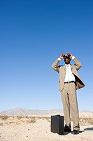 Businessman by briefcase using binoculars in desert, low angle view (thumbnail)