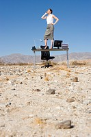 Businesswoman standing on desk in desert, on telephone, low angle view