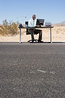Businessman at desk on side of road in desert, smiling, portrait, low angle view
