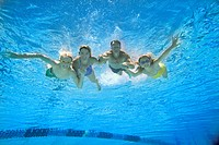 Family of four in swimming pool, smiling, portrait, underwater view