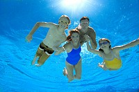 Family of four in swimming pool, smiling, portrait, underwater view lens flare