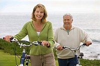 Mature couple with bicycles by sea, smiling, portrait