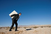 Businessman carrying filing cabinet on back in desert