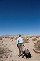 Businessman with luggage in desert, rear view