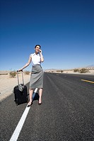 Businesswoman with luggage on mobile phone on road in desert, low angle view