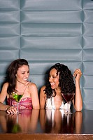 Young woman at table with cocktail, smiling at friend