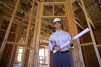 Young male architect with blueprint in partially built house, smiling, portrait, low angle view