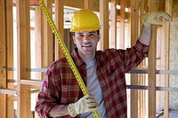 Builder in hardhat with tape measure in partially built house, smiling, portrait
