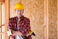 Builder in hardhat with drill in partially built house, smiling, portrait